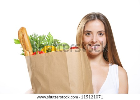 Portrait of smiling young woman holding a shopping bag full of groceries on white background - stock photo