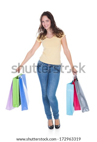 Portrait Of Smiling Young Woman Holding Shopping Bags Over White Background