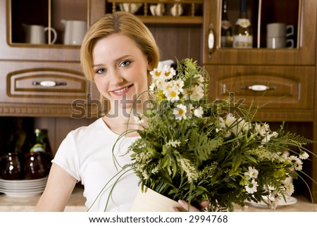 Portrait of smiling young woman holding the blossom - stock photo