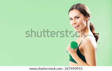 Portrait of smiling young woman in fitness wear exercising with dumbbell, over green background, with blank copyspace area for text or slogan - stock photo