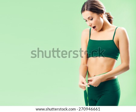 Portrait of smiling young woman in fitness wear with tape, with blank copyspace area for text or slogan, over green background - stock photo