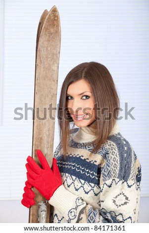 portrait of smiling young woman in winter sweater holding old wooden ski - stock photo