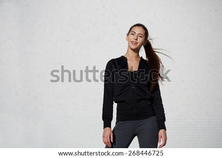 Portrait of smiling young woman ready for workout standing with dynamic flying hair on white wall background at beautiful sunny day, athletic healthy girl dressed in sportswear posing outdoors - stock photo