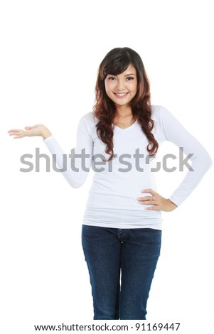 Portrait of smiling young woman showing a imaginary product on white background - stock photo