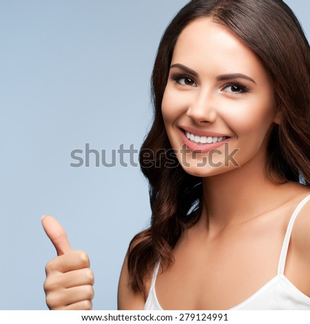 Portrait of smiling young woman showing thumb up gesture, against grey background - stock photo