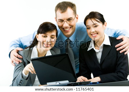 Portrait of smiling young woman sitting at the table with their leader standing behind them and looking at laptop screen together - stock photo