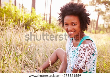 Portrait Of Smiling Young Woman Sitting In Countryside - stock photo