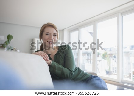 Portrait of smiling young woman sitting on the couch at home