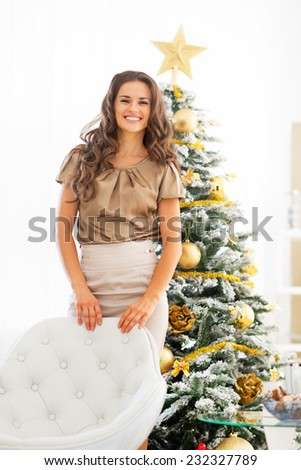 Portrait of smiling young woman standing near christmas tree - stock photo