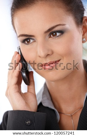 Portrait of smiling young woman talking on mobile phone. - stock photo