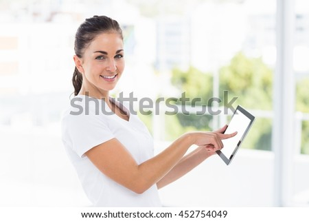 Portrait of smiling young woman using digital tablet at home