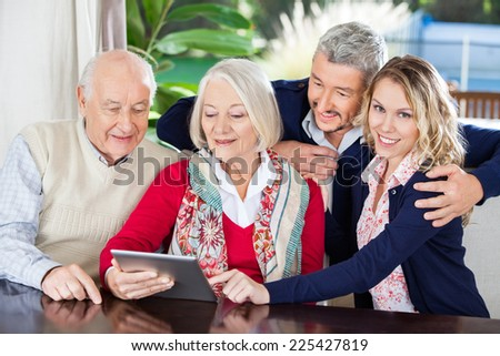 Portrait of smiling young woman using digital tablet with family at nursing home - stock photo