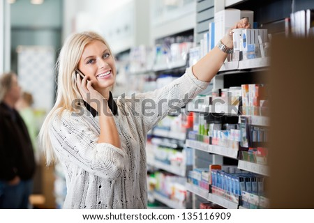 Portrait of smiling young woman using mobile phone in pharmacy - stock photo