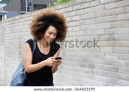 Portrait of smiling young woman walking and looking at cellphone - stock photo