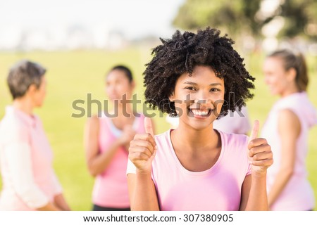 Portrait of smiling young woman wearing pink for breast cancer in front of friends in parkland - stock photo