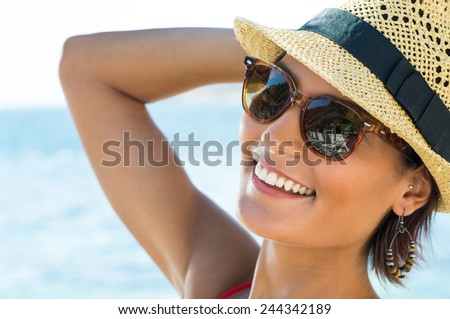 Portrait Of Smiling Young Woman Wearing Sunglasses - stock photo
