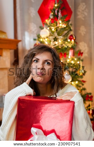 Portrait of smiling young woman with a gift box, not satisfied with her gifts over living room - stock photo
