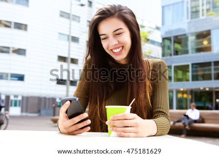 Portrait of smiling young woman with cellphone and coffee