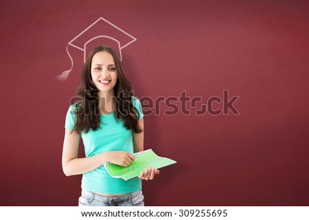 Portrait of smiling young woman with file against red background - stock photo