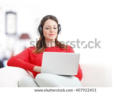 Portrait of smiling young woman with laptop sitting at home and listening music while relaxing on sofa. - stock photo