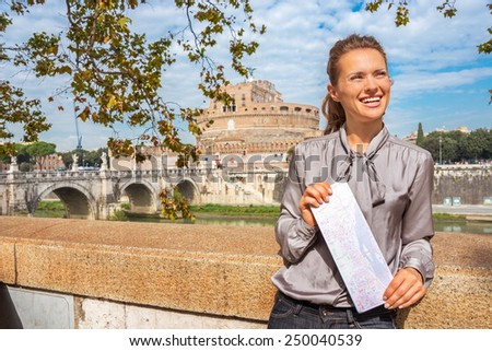 Portrait of smiling young woman with map on embankment near castel sant'angelo in rome italy - stock photo