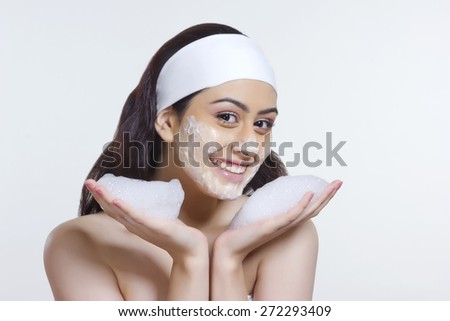 Portrait of smiling young woman with soap sud over white background - stock photo