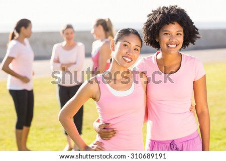 Portrait of smiling young women wearing pink for breast cancer in parkland - stock photo