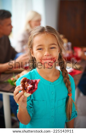 Portrait of smudgy girl eating sweet pie on background of her parents - stock photo