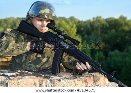 Portrait of sniper in camouflage uniform in action - stock photo