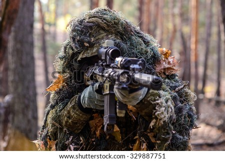 Portrait of sniper in the woods, which  aiming from his rifle/Sniper aiming from his rifle in forest - stock photo