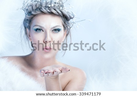 Portrait of snow queen blowing in her palm - stock photo