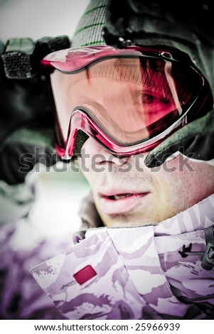 Portrait of snowboarder looking at camera through eyeglasses - stock photo