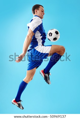 Portrait of soccer player jumping with ball on a blue background - stock photo