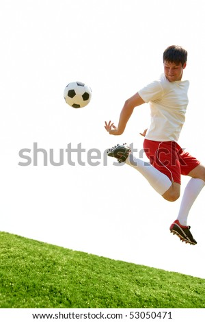 Portrait of soccer player jumping with ball over football field - stock photo
