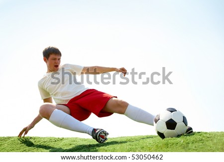 Portrait of soccer player kicking ball during game - stock photo