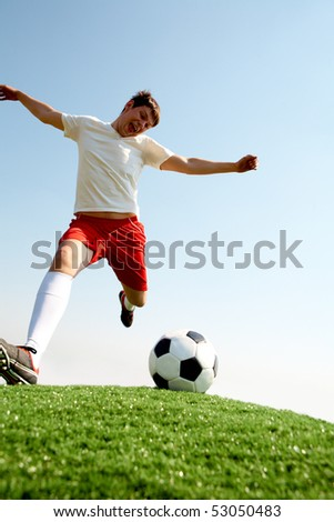 Portrait of soccer player kicking ball on football field - stock photo