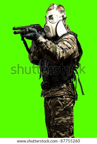 portrait of soldier aiming with shotgun against a removable chroma key background - stock photo