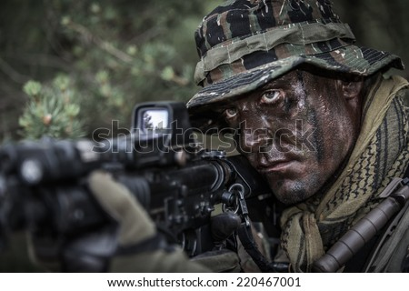 portrait of soldier dressed in tiger stripe camouflage with assault rifle - stock photo