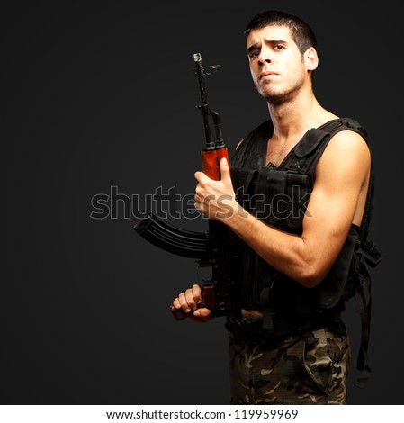 Portrait Of Soldier Holding Gun against a black background