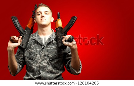 Portrait Of Soldier Holding Gun On red Background - stock photo