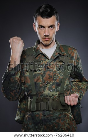 portrait of soldier in camouflage and ammunition fighting. studio shot - stock photo
