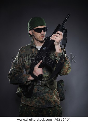 portrait of soldier in camouflage and ammunition with a rifle. studio shot - stock photo