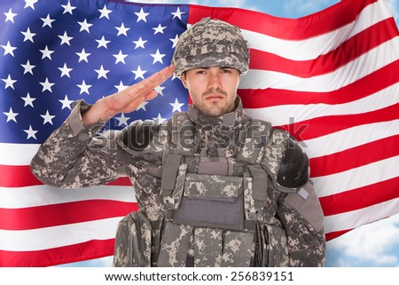 Portrait Of Soldier Saluting In Front Of American Flag - stock photo