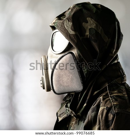 portrait of soldier wearing gas mask over abstract background - stock photo