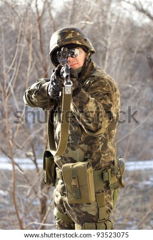 Portrait of soldier with a gun in his hands - stock photo
