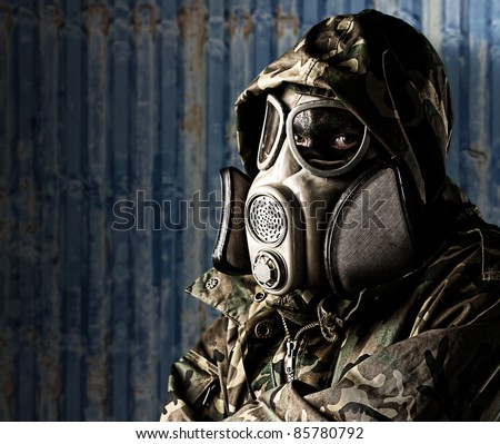 portrait of soldier with gas mask and rifle against a ship container - stock photo