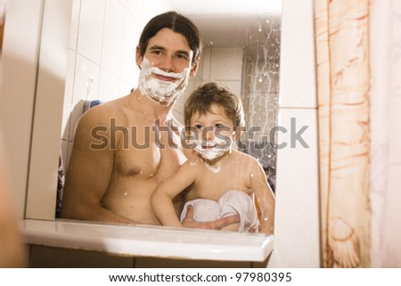 Portrait of son and father enjoying while shaving together - stock photo
