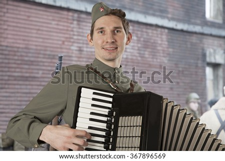 Portrait of Soviet soldier in uniform of World War II playing the accordion outdoors  - stock photo