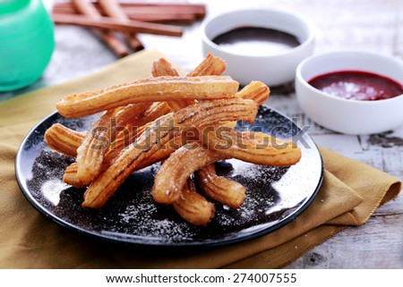 portrait of spanish tapas churros served with chocolate and blueberry sauce - stock photo