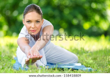 Portrait of sportive woman stretching herself in park. Concept of healthy lifestyle and fitness
